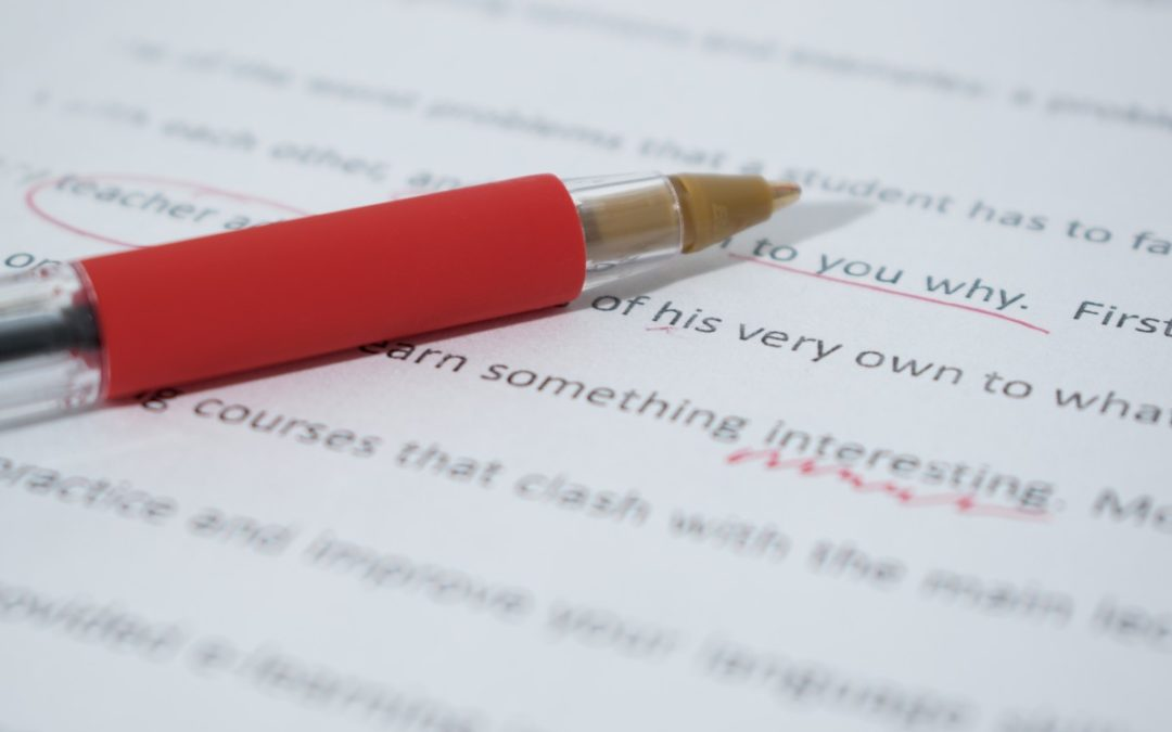 A red pen on a document with some mistakes which have been corrected